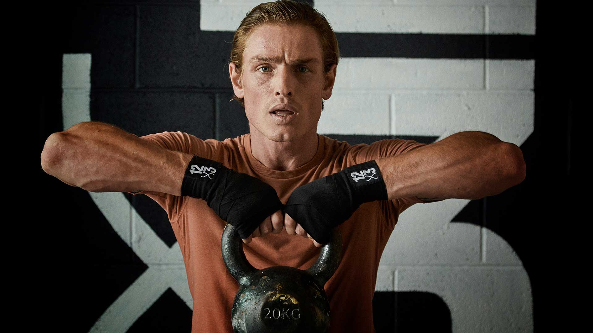 man pulling up weight in gym
