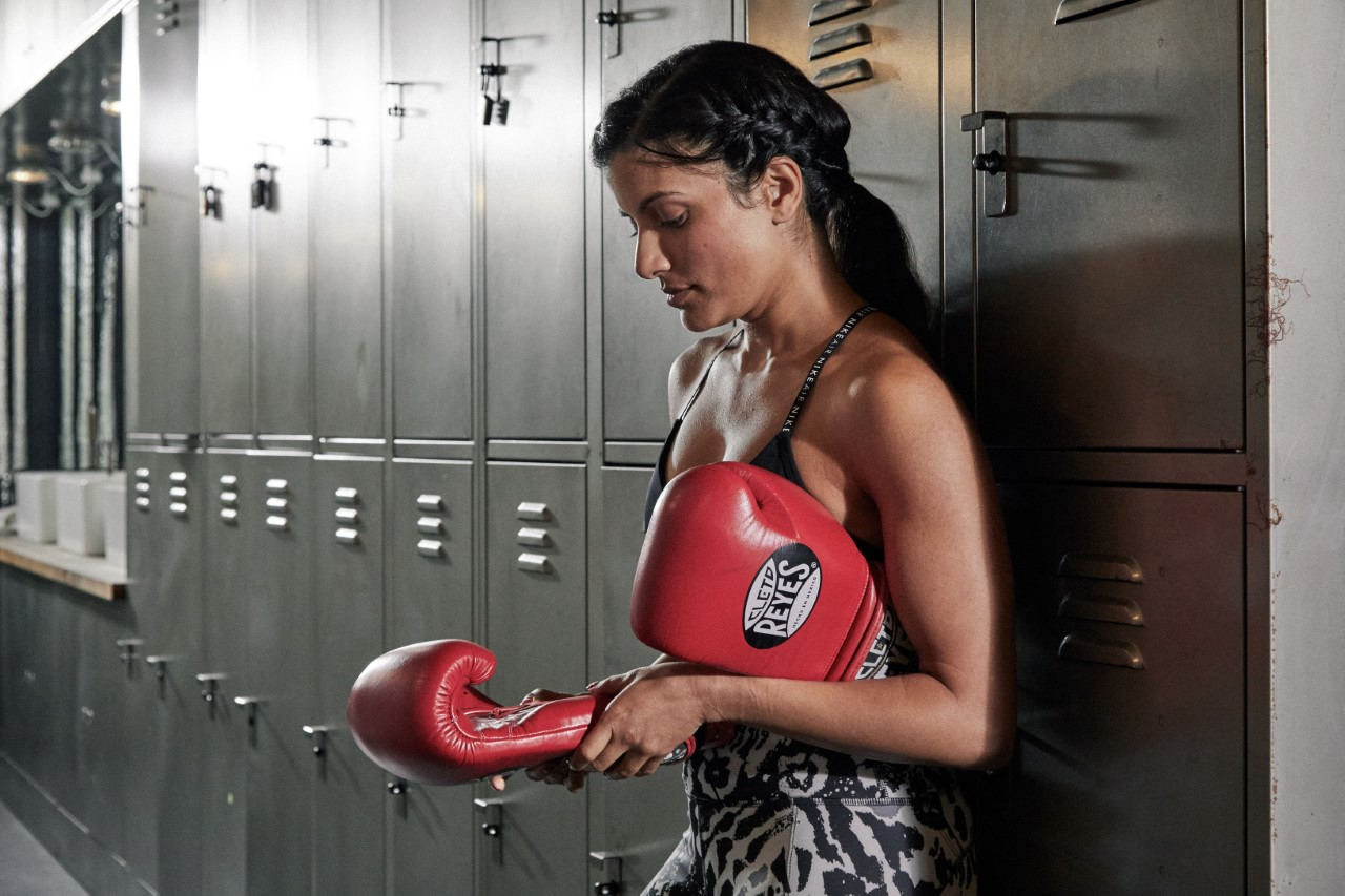 female looking at boxing gloves in locker room