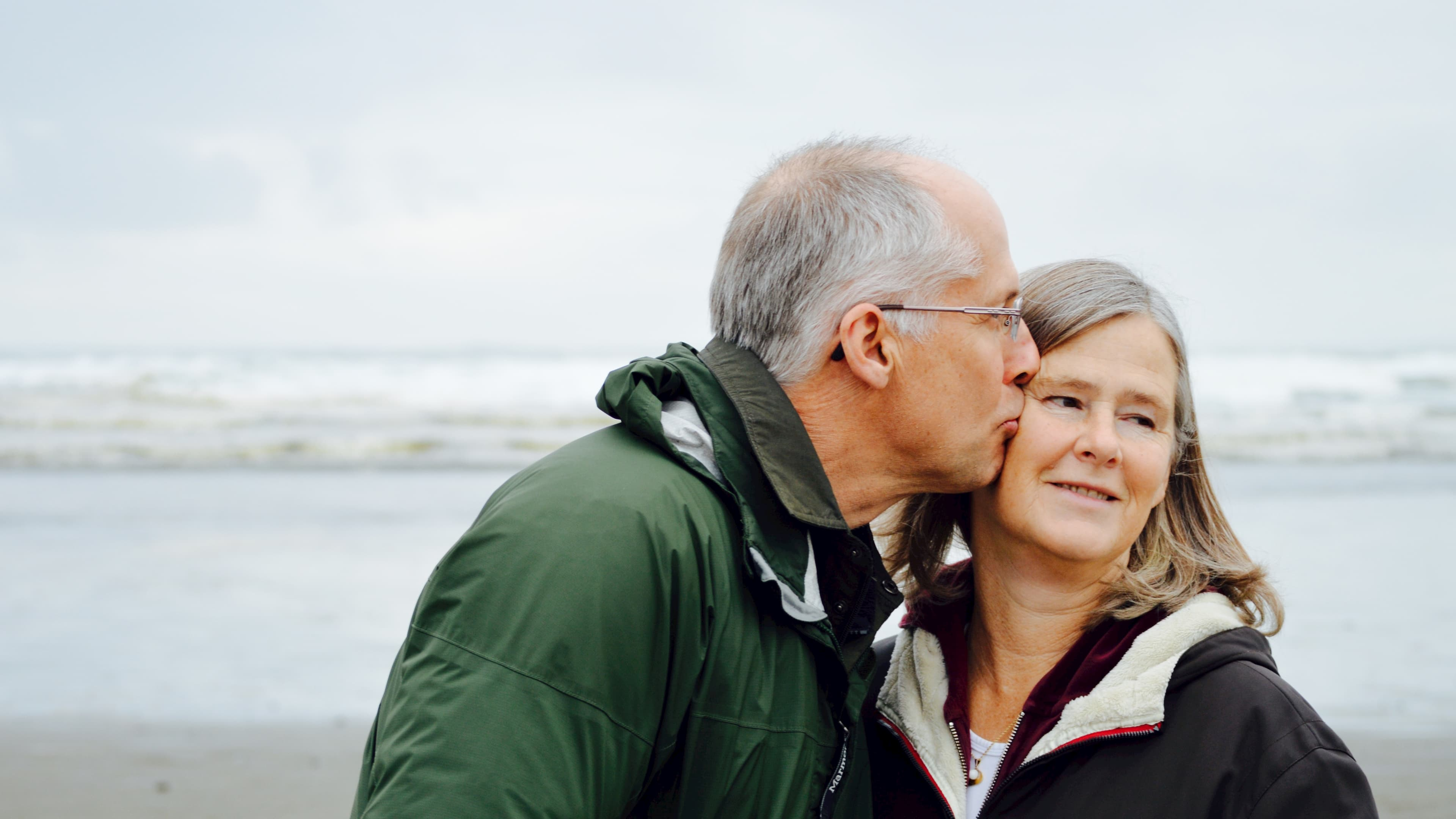 Elderly man kissing elderly woman on cheek in front of beach on cold day
