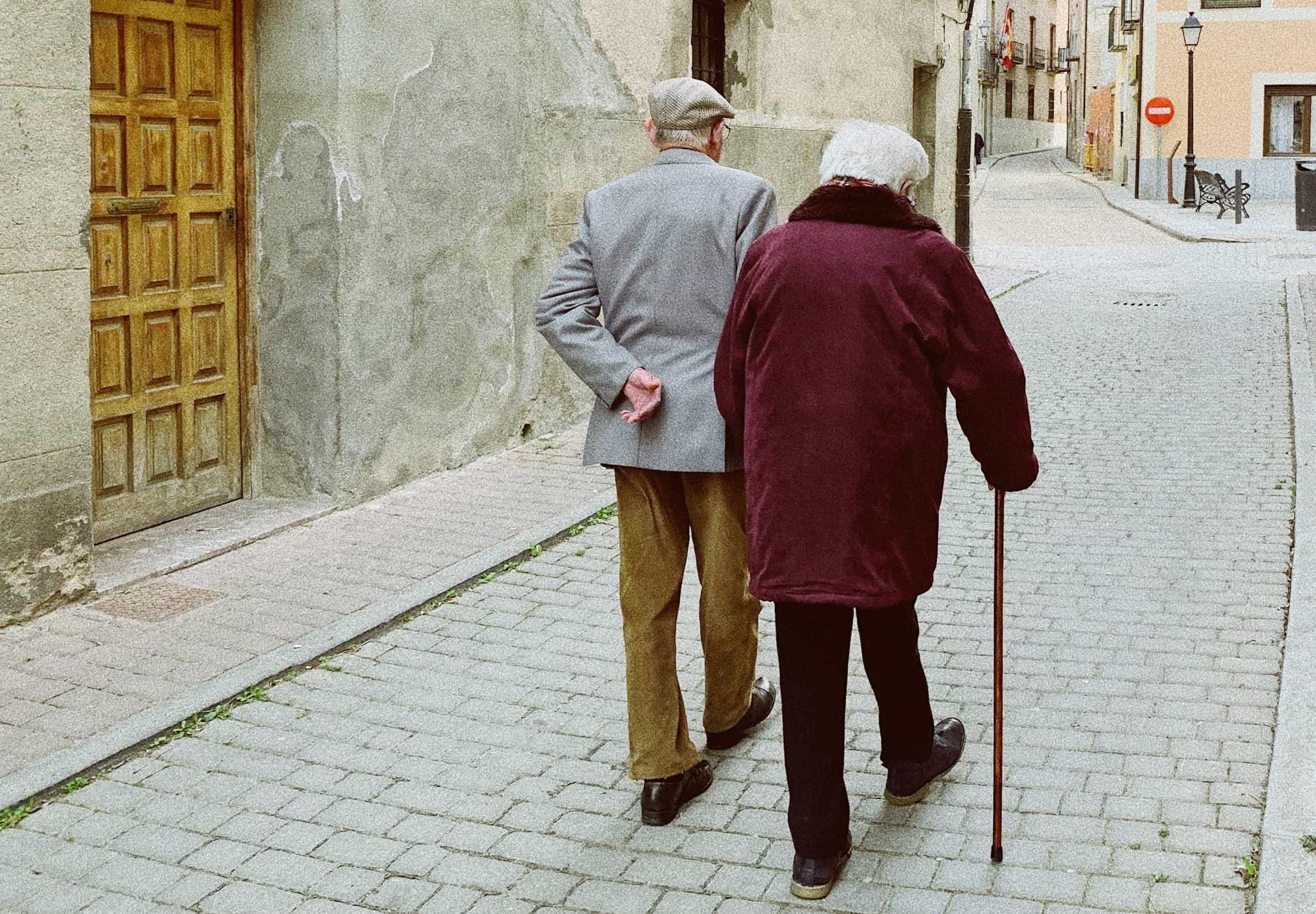 Elderly man and woman walking down cobblestone street