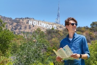 Man with sunglasses and a shirt next to the Hollywood Sign.