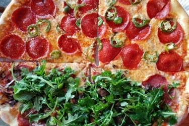 Half pepperoni pizza with jalapeños and half pepperoni pizza with arugula on top