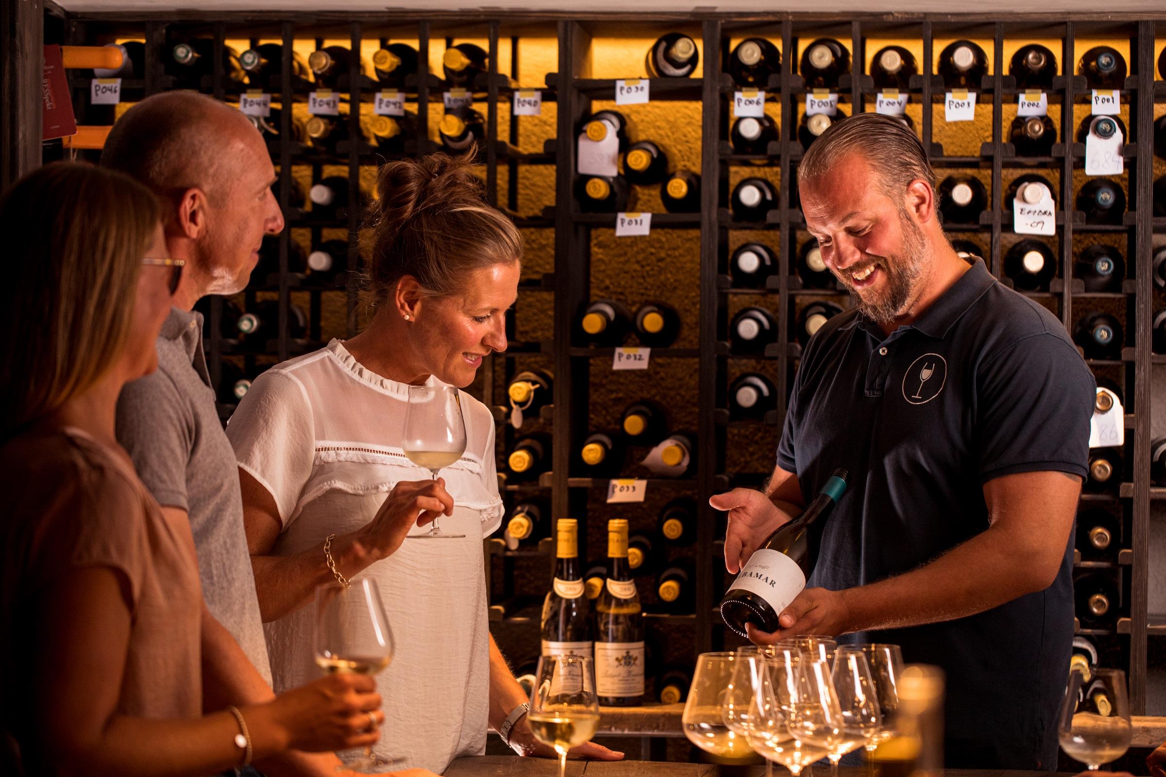 Man viser frem en flaske med vin til tre mennesker som følger interessert med