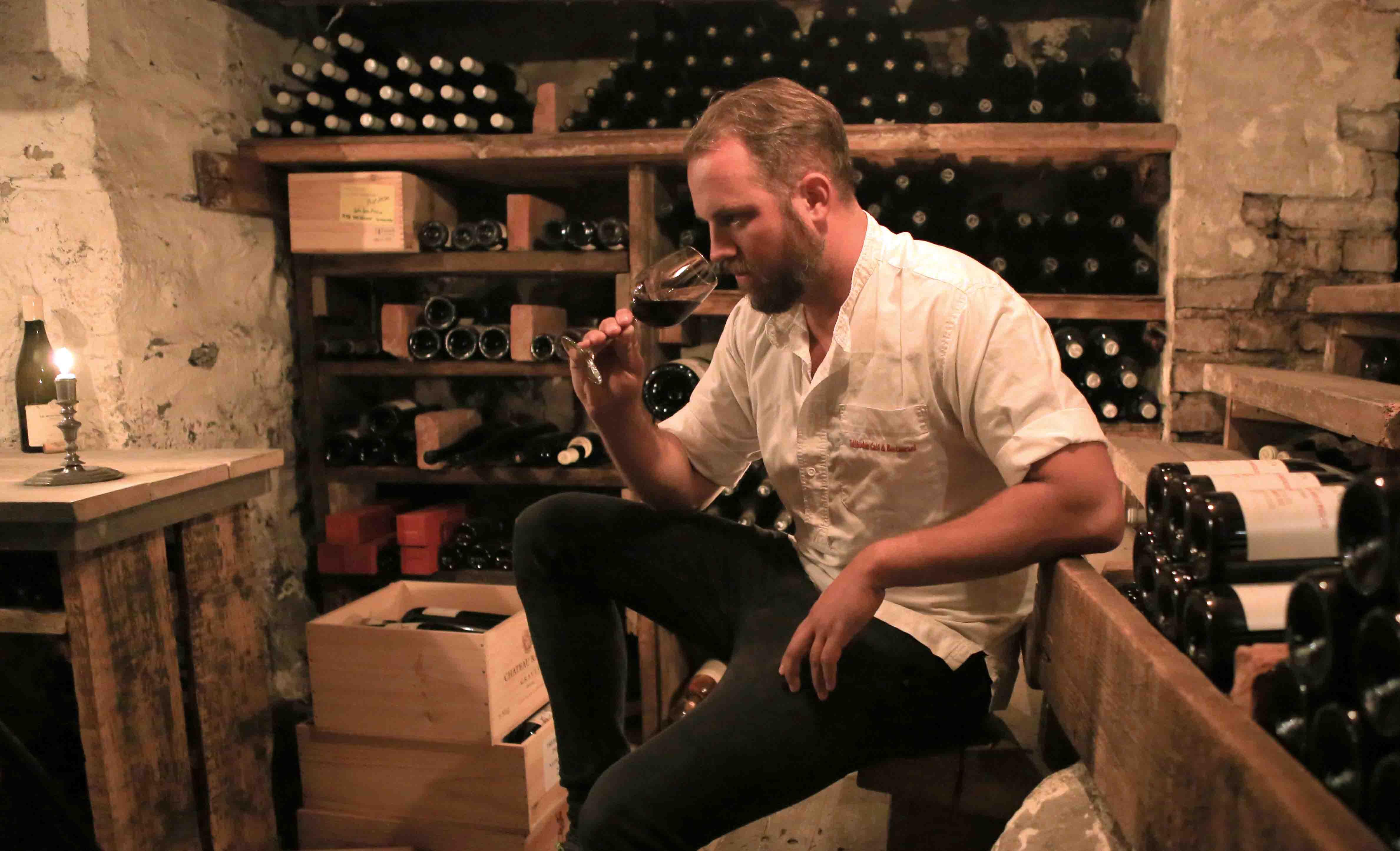 mann som lukter på vin i en vinkjeller omgitt av flasker
