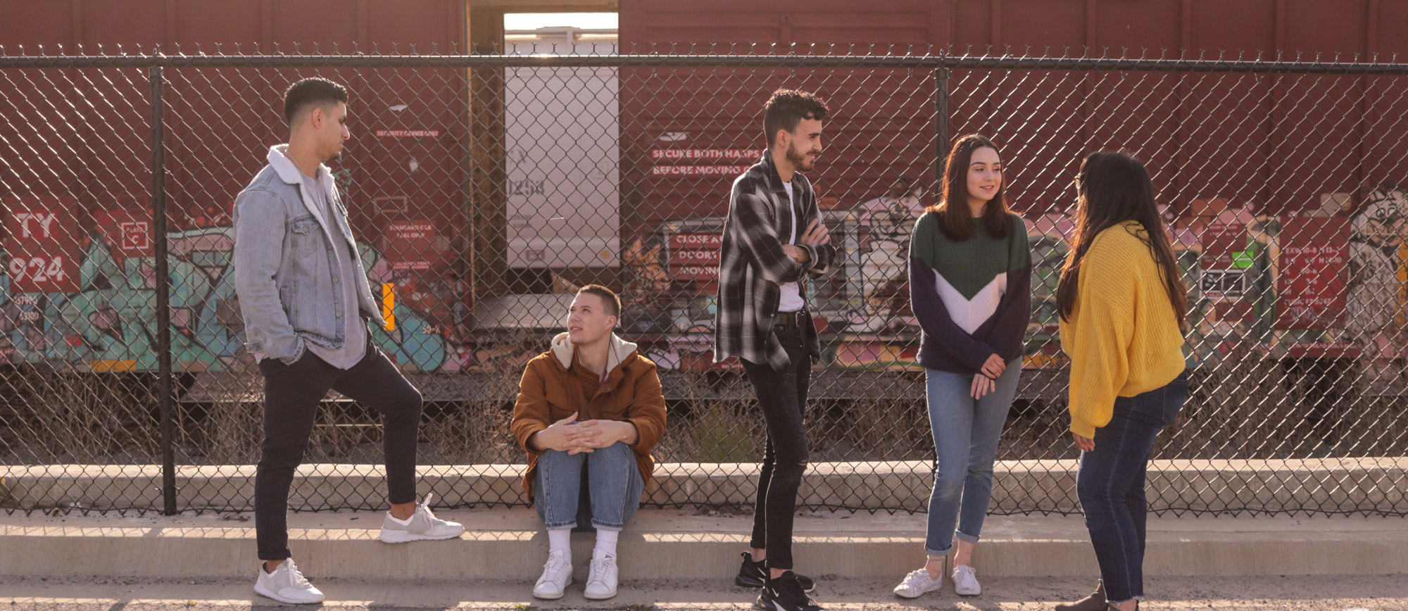 Five people in front of chain link fence talking