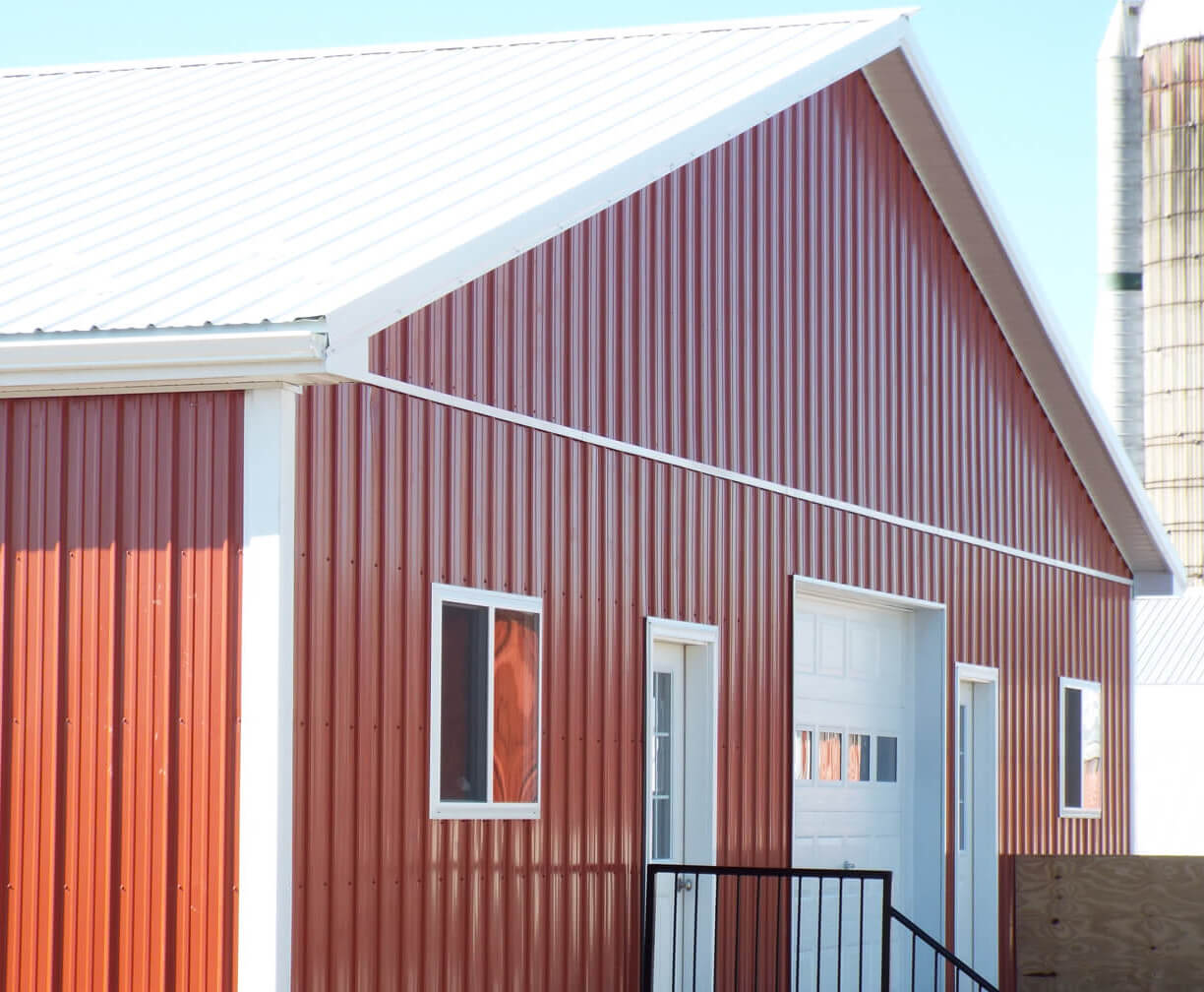 A red pole barn with a white metal roof.