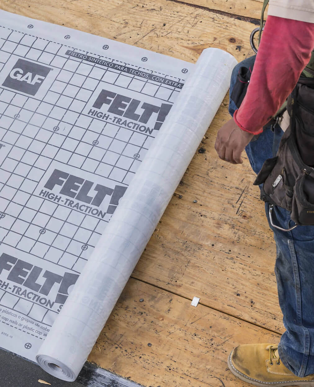 A roofer laying down GAF underlayment.