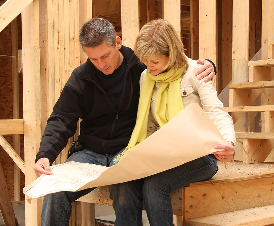 A man and woman sitting in a framed house reviewing building plans.