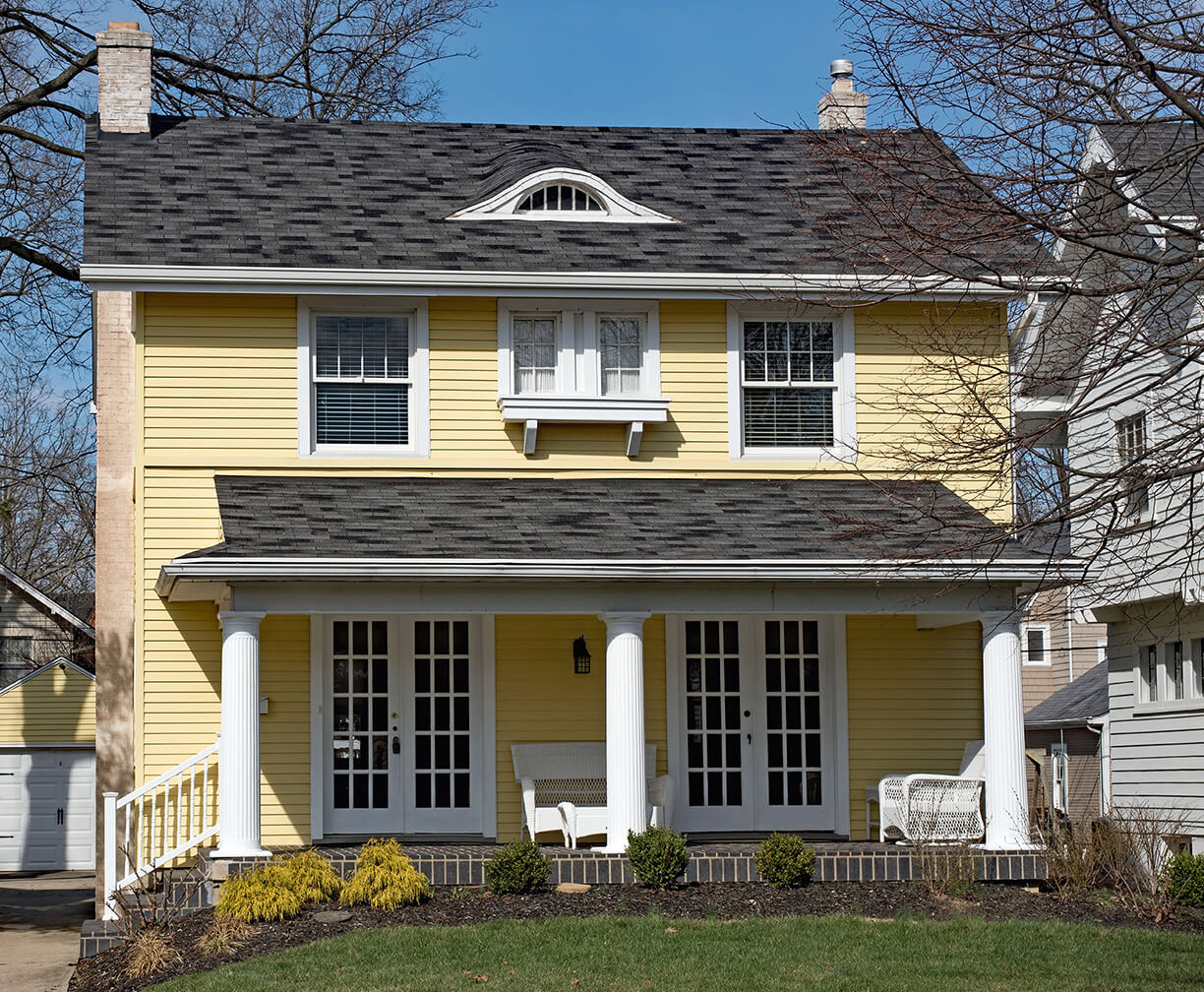 A new house with yellow siding, white trim, and a charcoal shingle roof.