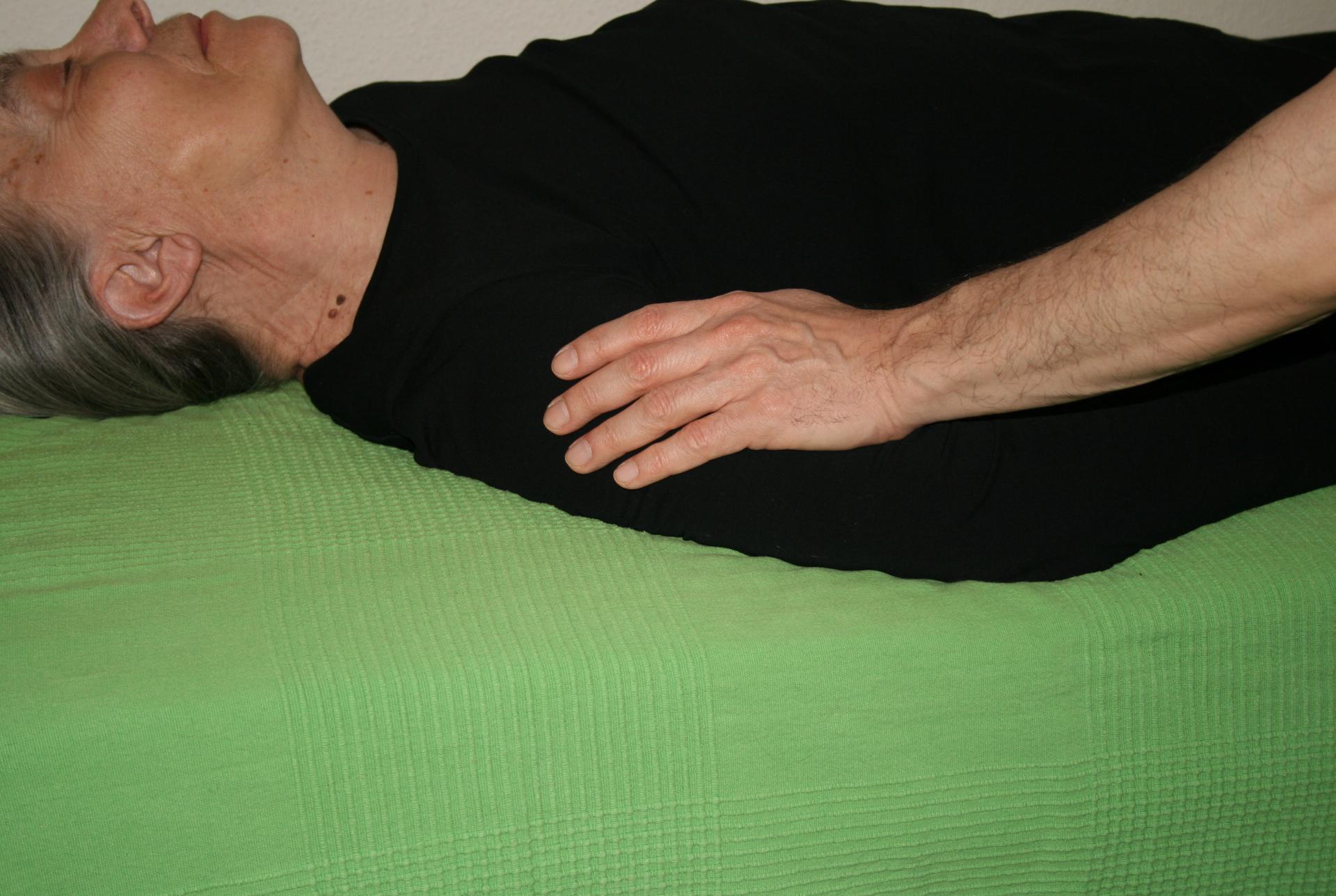 Billedet viser en en klient, der får behandling mod smerter i overarmen.