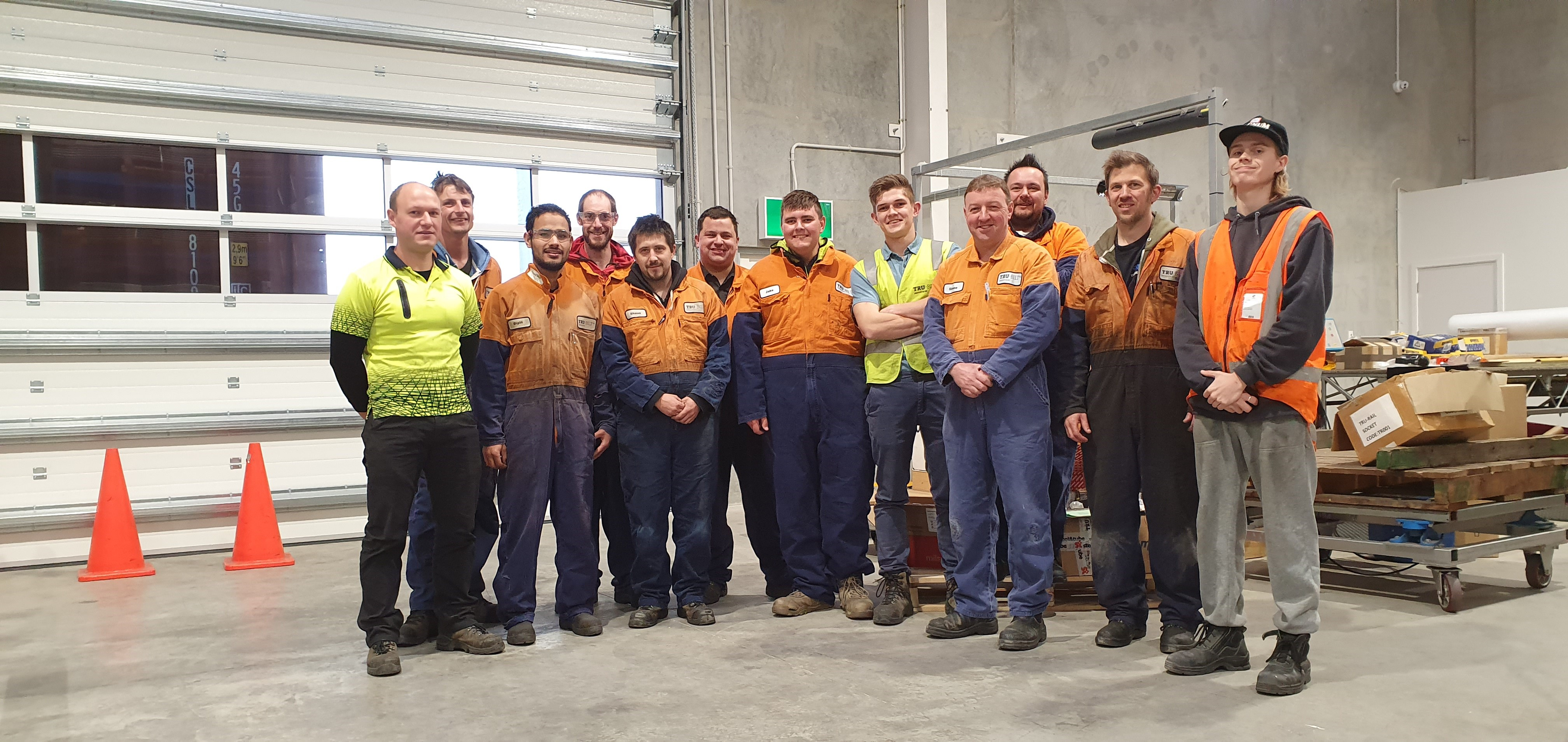 Jake Miller (pictured in centre) works with a IDEA Services vocational support worker to make a success of his job with Tru-Bilt Industries.