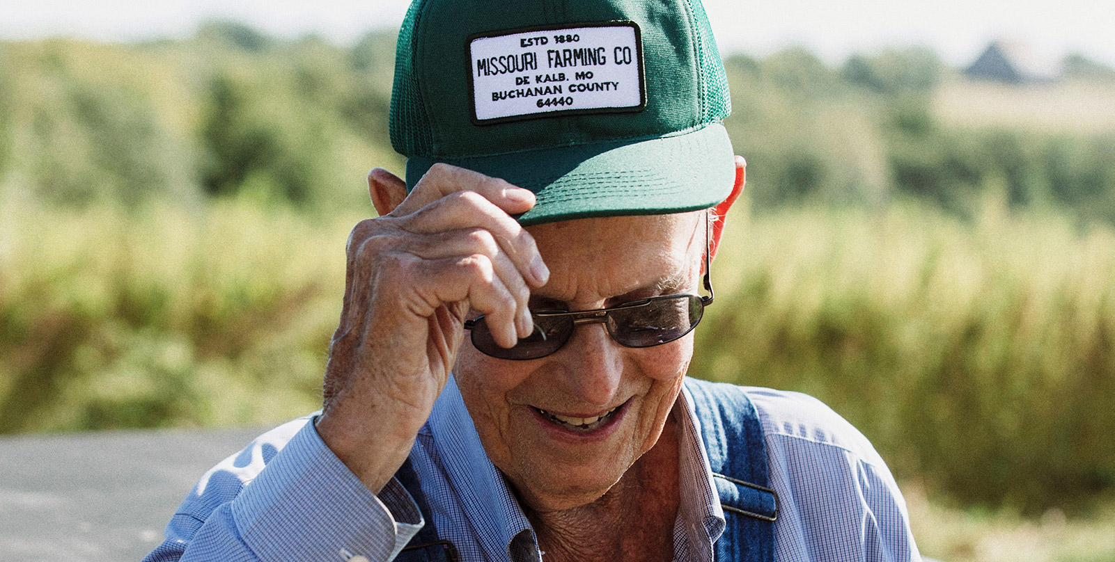 One of four generations of farmers adjusting his signature Missouri Farming Company hat.