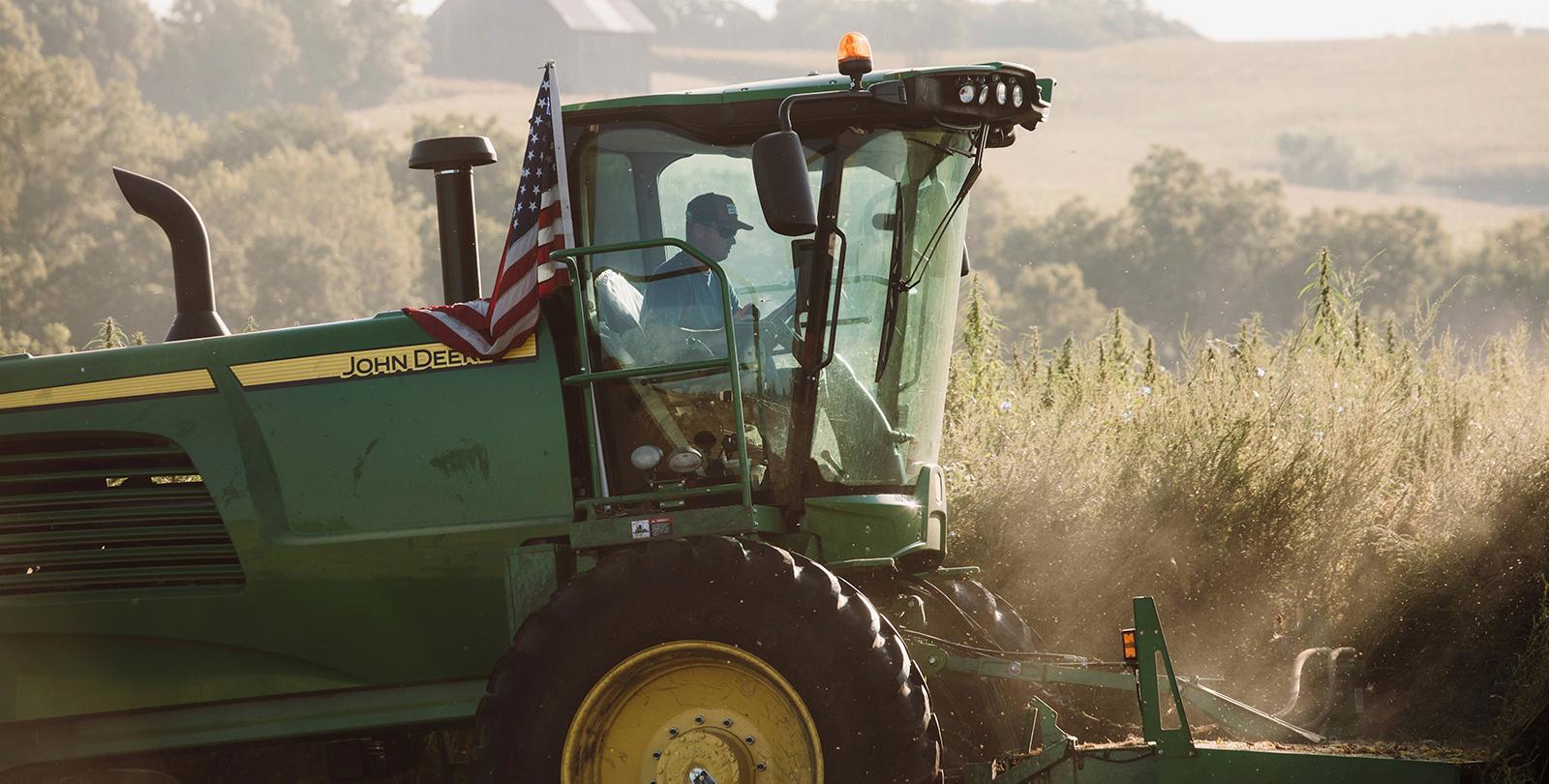 Remington operating a John Deere tractor on our hemp farm in Buchanan County.