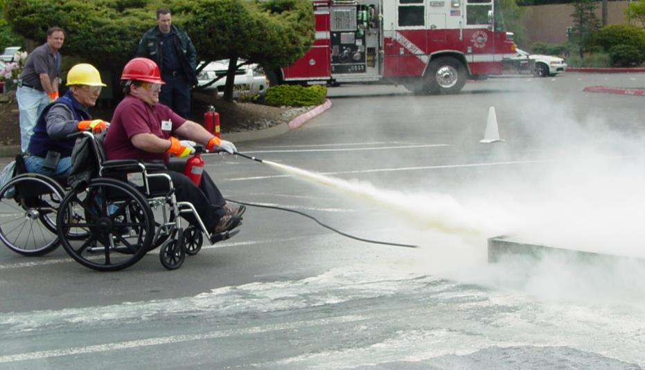 two men in wheelchairs practice using a fire extinguisher