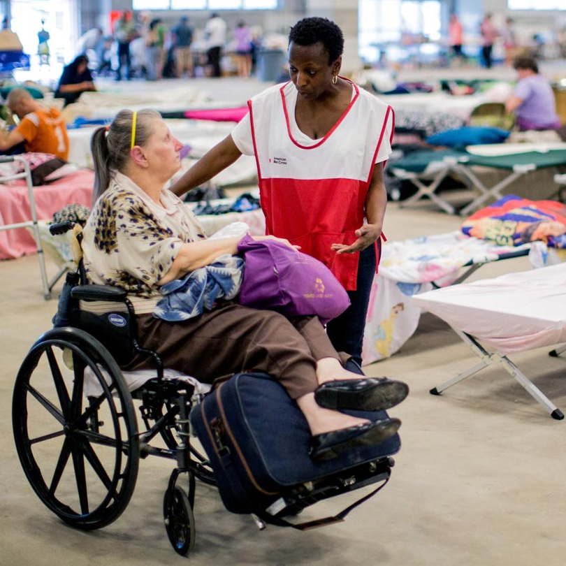 woman in wheelchair and volunteer speaking in emergency shelter with cots