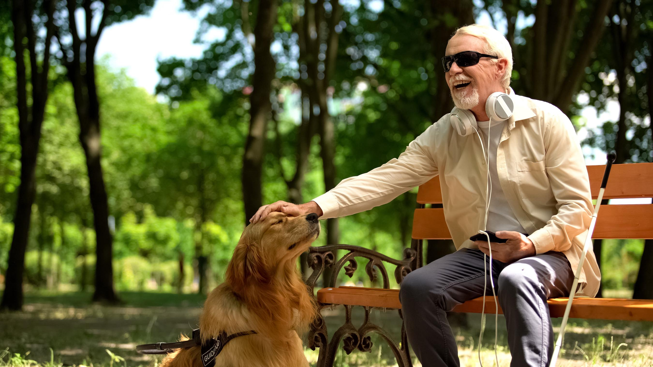 Blind white haired man wears sunglasses and headphones while petting his dog from a scenic park bench