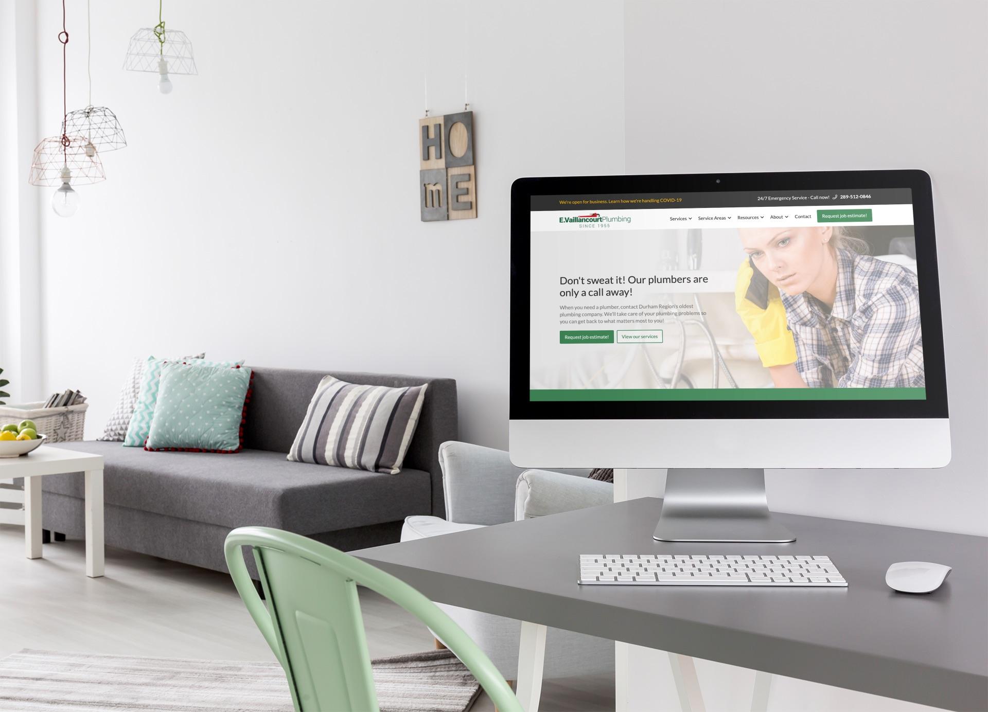 iMac on desk displaying vaillancourtplumbning.ca website