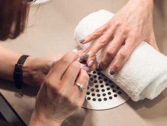 Deux mains avec la pose de vernis sur les ongles