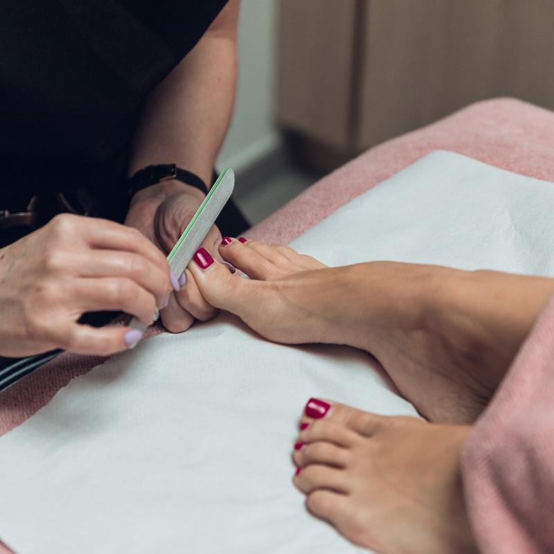 Femme qui se fait limer les ongles de pieds