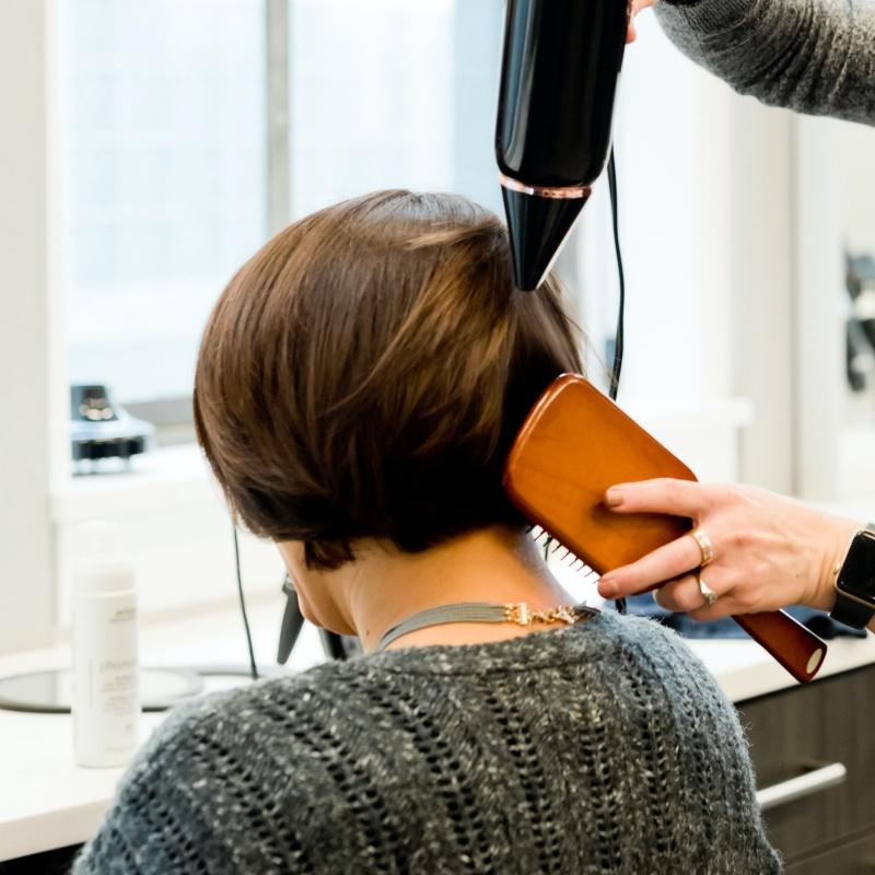 Femme qui se fait sécher les cheveux