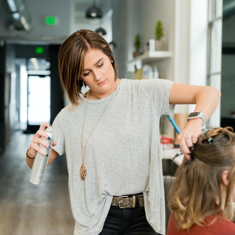 Femme qui se fait laquer les cheveux