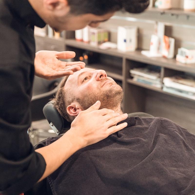 Deux hommes, un coiffeur qui applique le soin sur la barbe du client