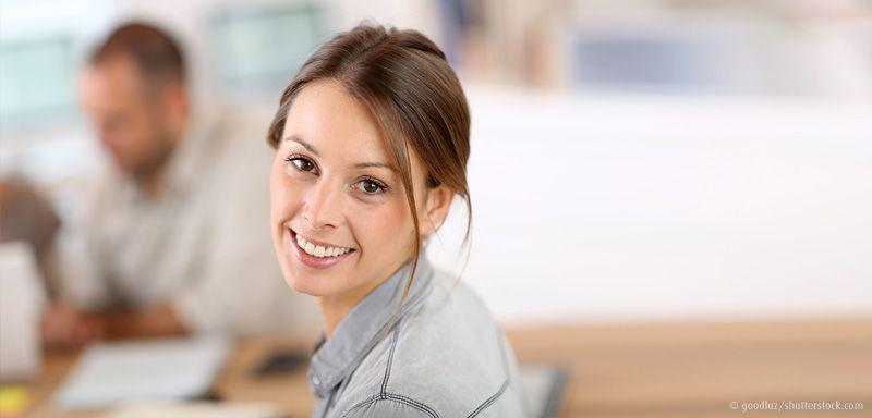 Junge Frau lacht mit Kollegen