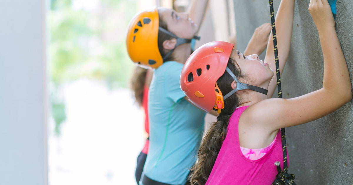 A girl in a pink shirt and a boy in a blue shirt rock climbing in orange helmets.