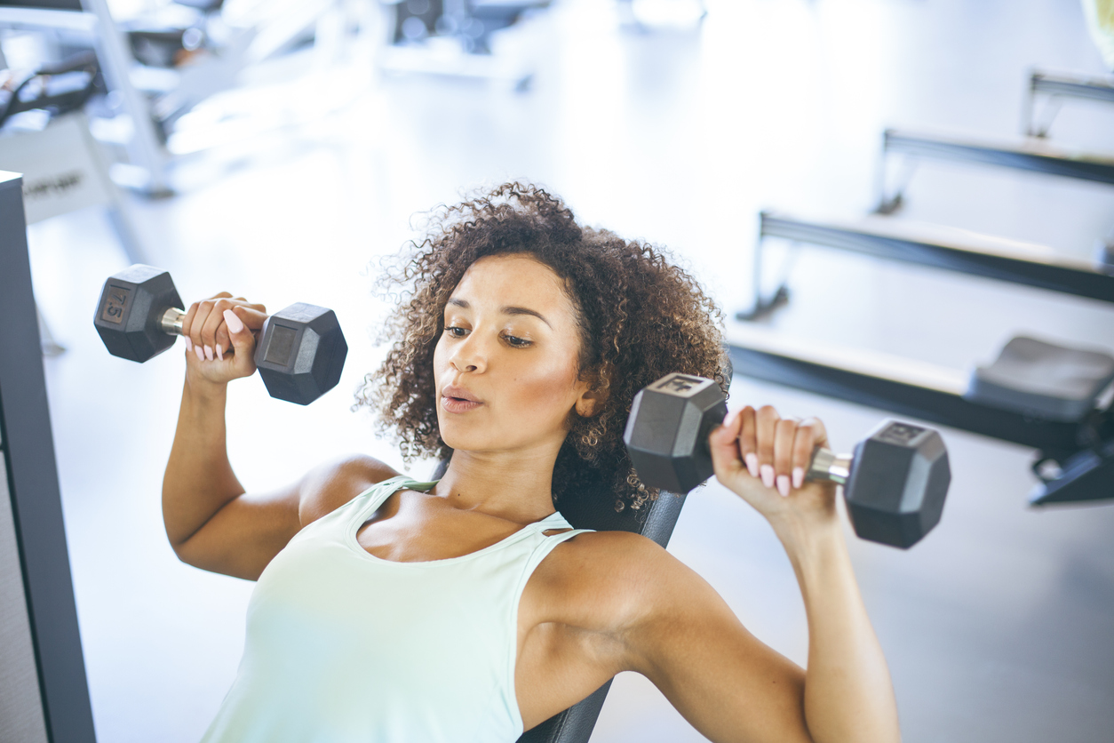 women working out in gym lifting weights