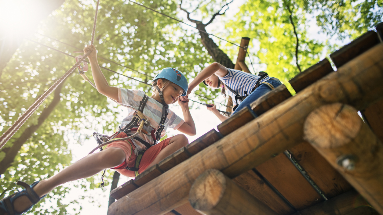 Camper shows kindness to peer by offering a helping hand on rope climbing obstacle course.