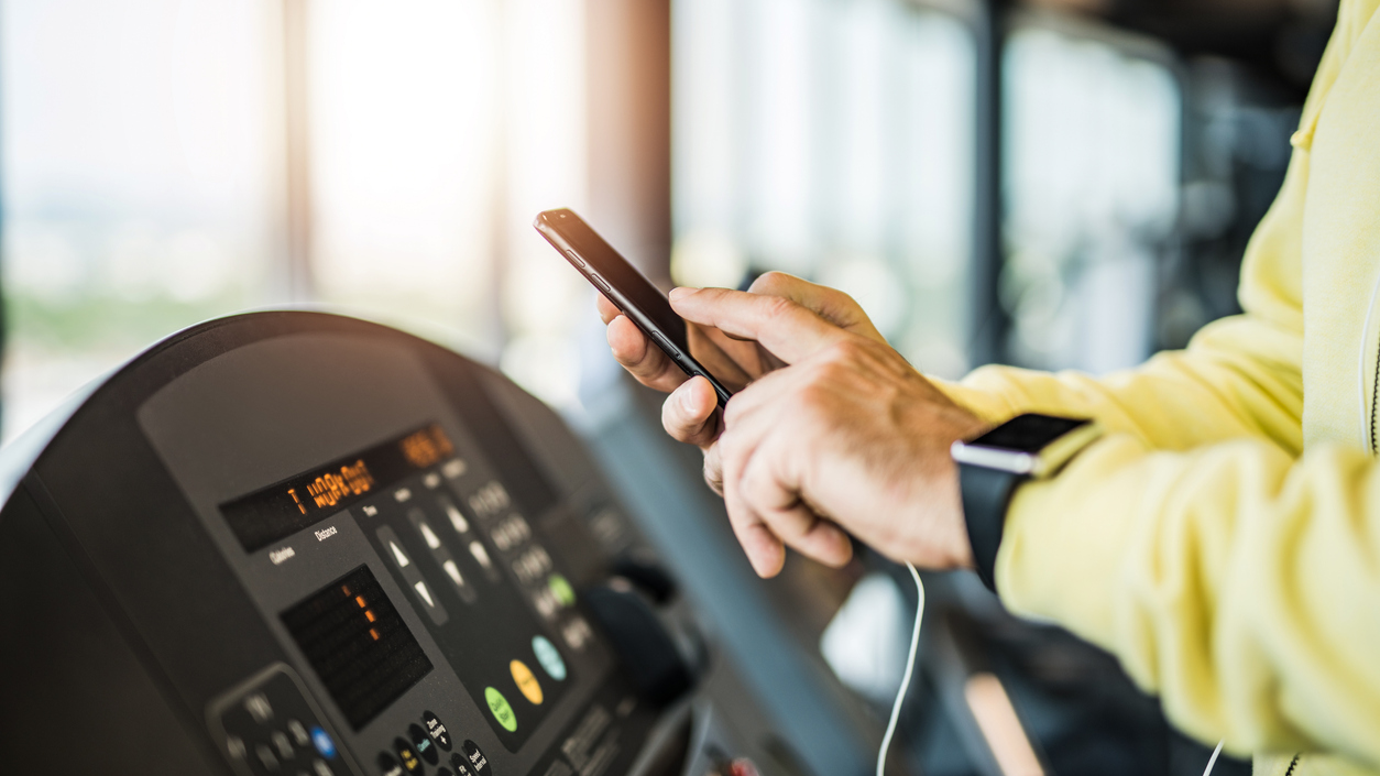 Man in yellow sweatshirt on phone at the gym, while on treadmill.