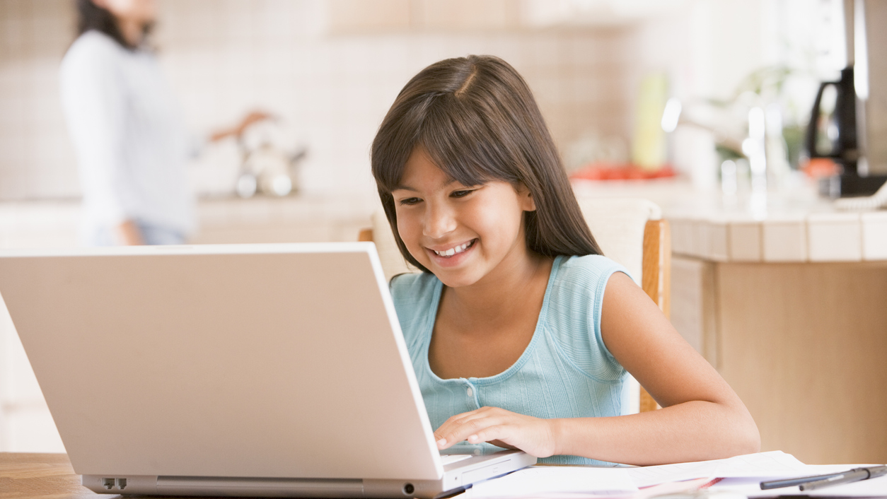 Girl sitting at kitchen table on a laptop.