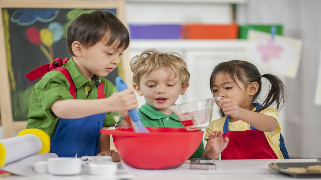 Three children cooking in a classroom.