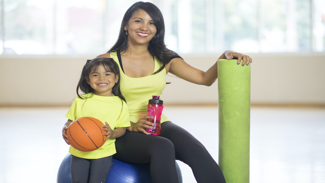 Mother and daughter in yellow shirts at a gym with foam roller and basketball.