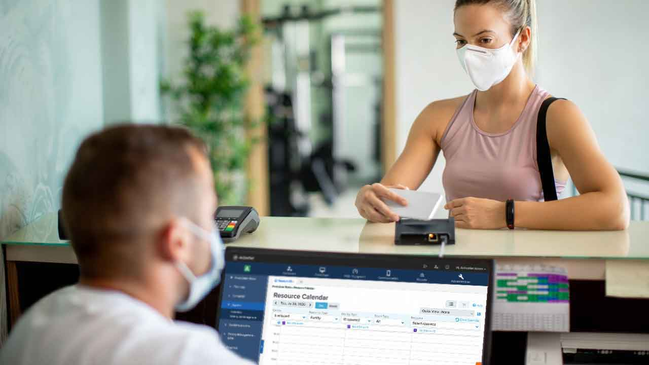 Woman in pink tank top and face mask checking into rec center as man sits at desk in face mask in front of computer.