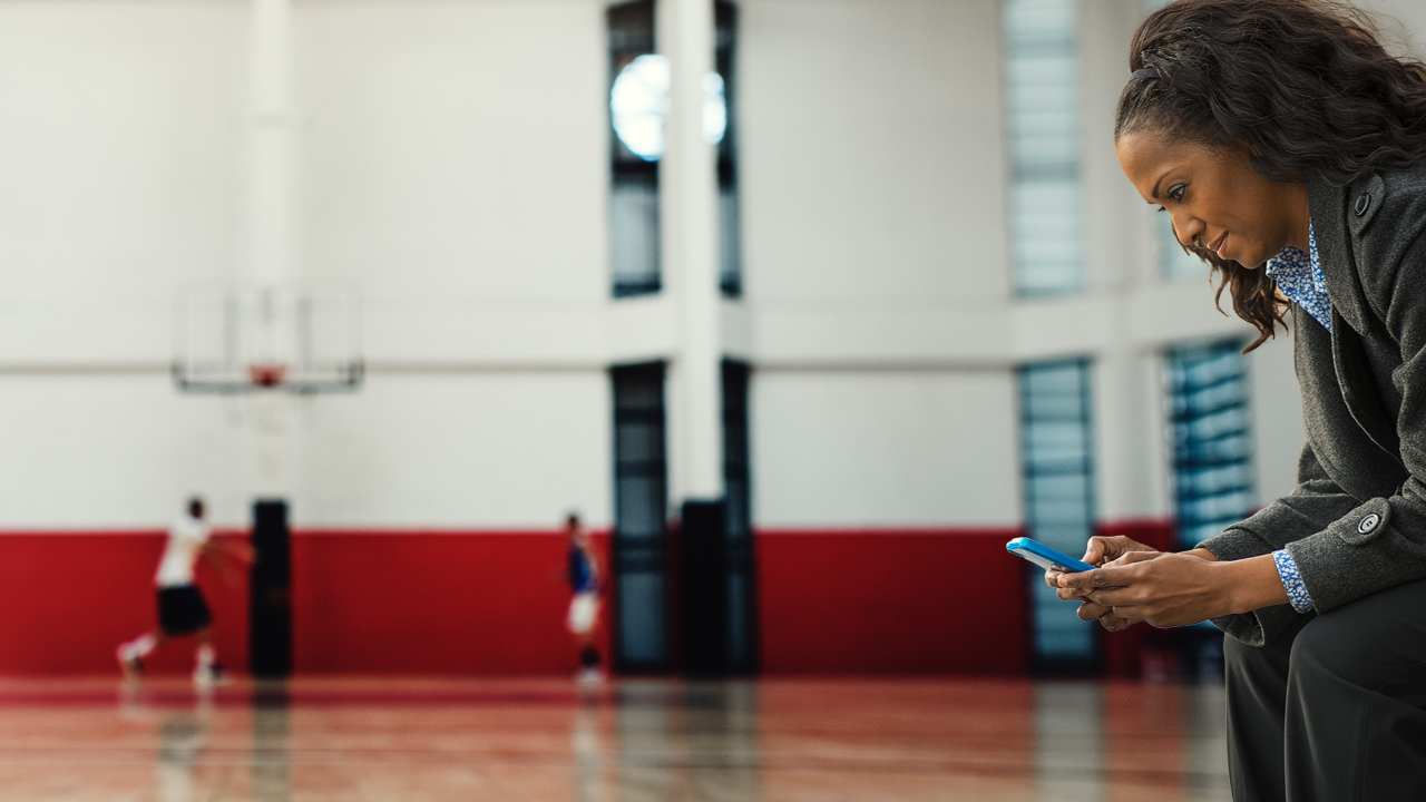 Woman sitting on a bench leaning forward while looking at her smartphone in a gymnasium.