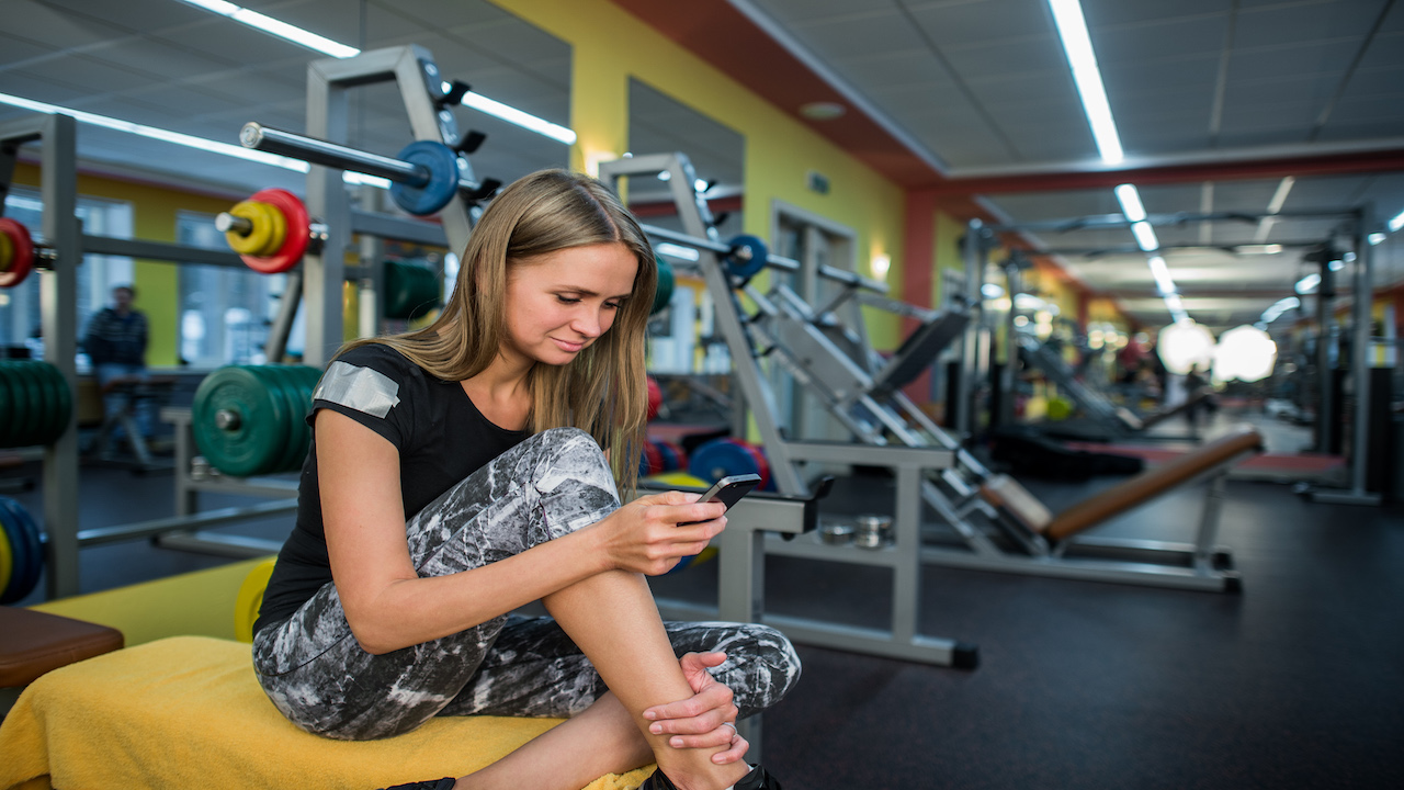 Woman at a gym looking at her smartphone.