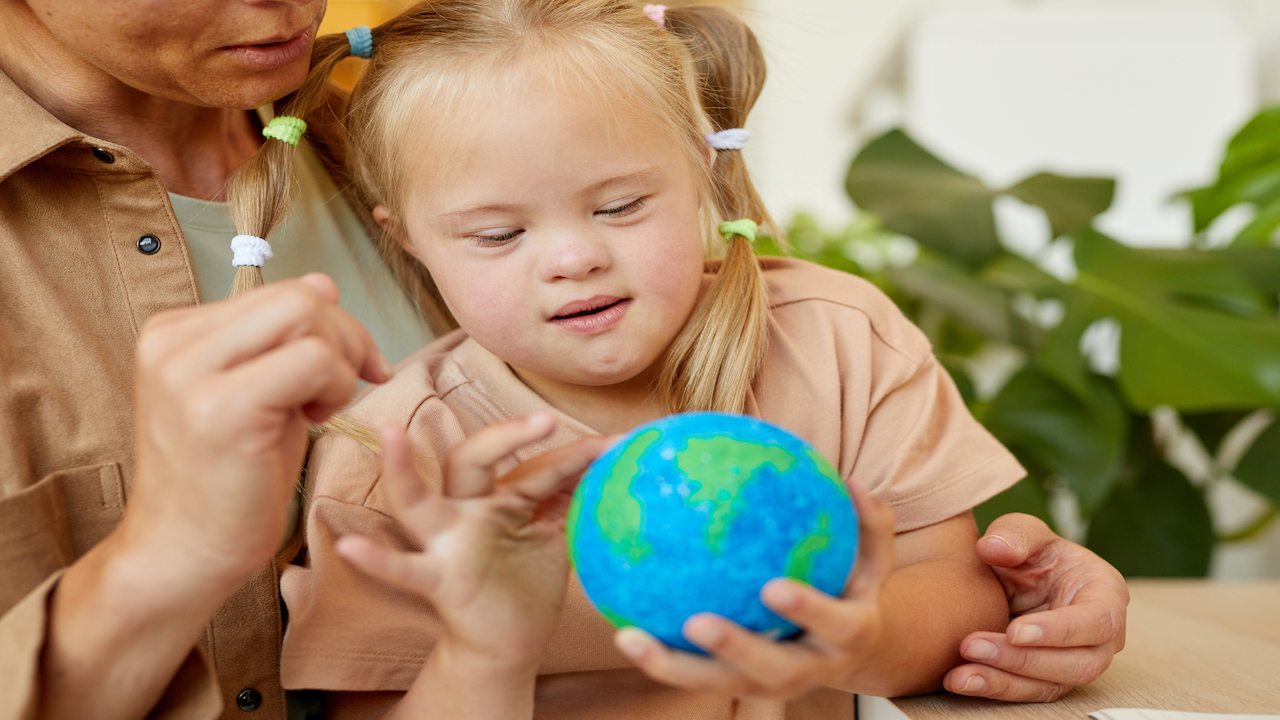 Young girl with Downes Syndrome sitting in an adults lap holding a small globe.