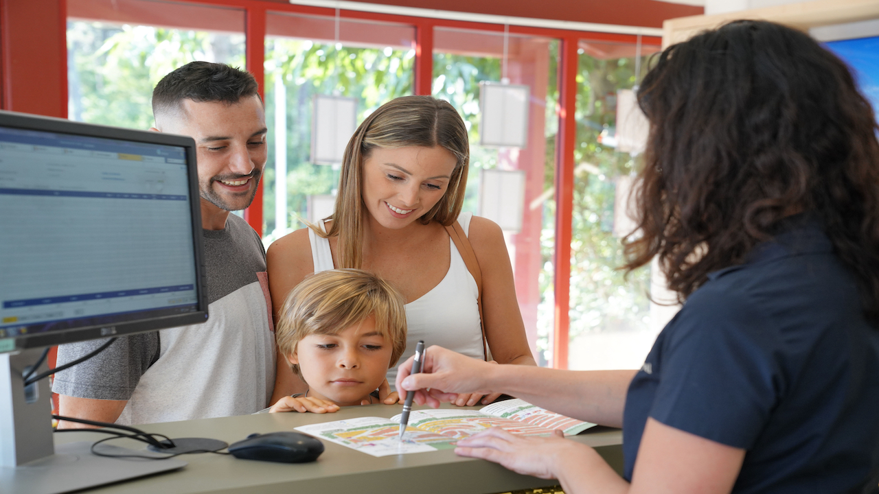Parents checking in their child into summer camp at front desk.