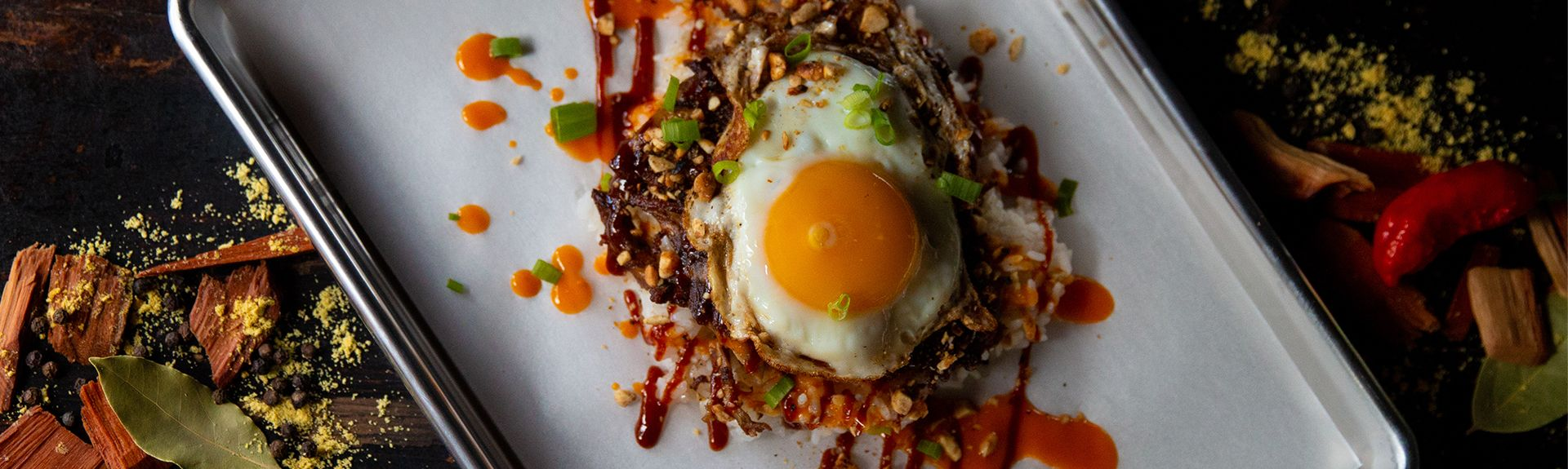 Sunny side up egg over crispy pulled pork on white rice
