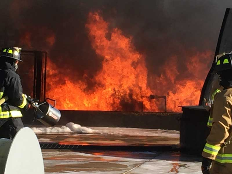 two firemen putting out an industrial fire