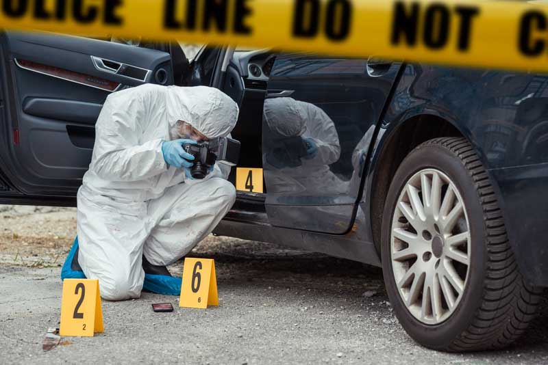 man taking photos at crime scene with hazard suit on