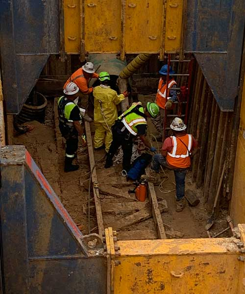 construction workers in a confined space working on a project
