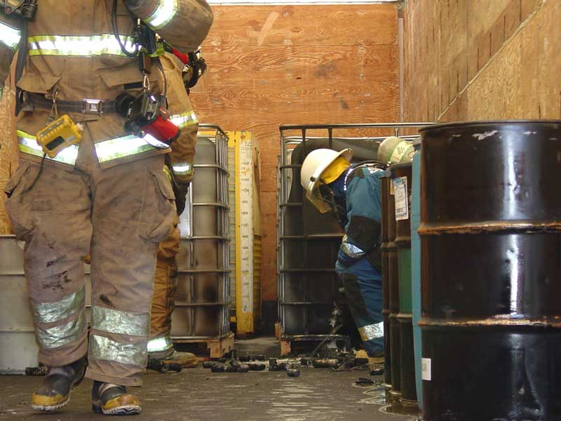 men cleaning a dangerous area with haz mat suits on