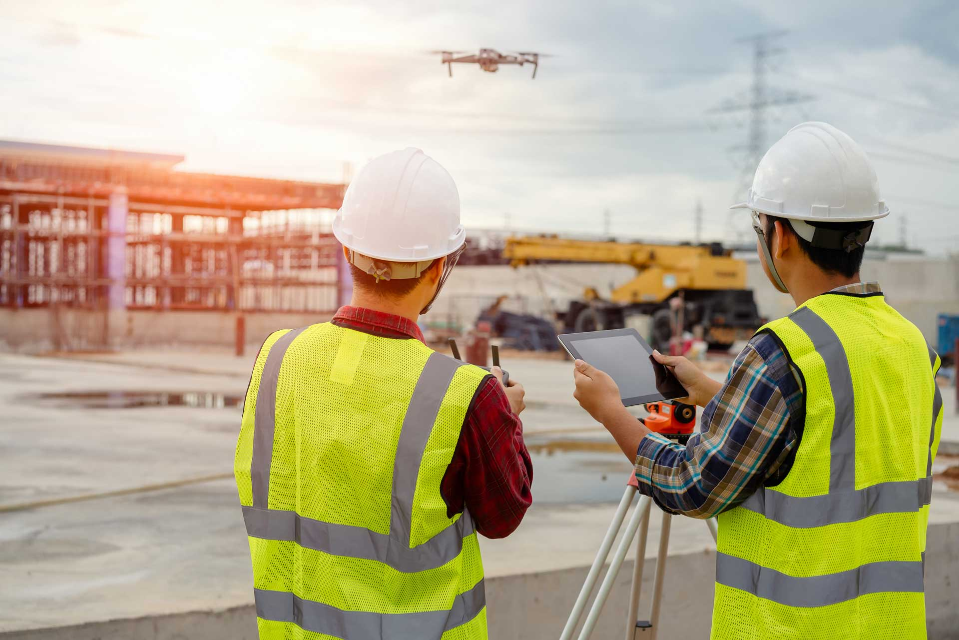 men in construction suites flying a drone