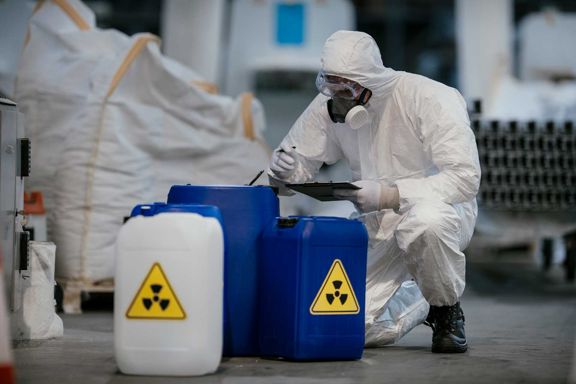 man in hazard suite checking barrels of hazardous product