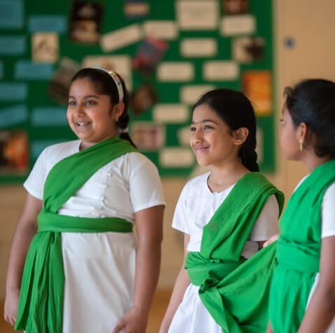 two bharatanatyam girls cheekily smiling