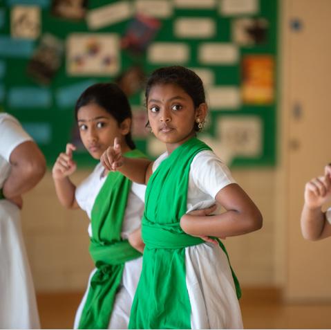 a bharatanatyam dancer confidently dancing in class
