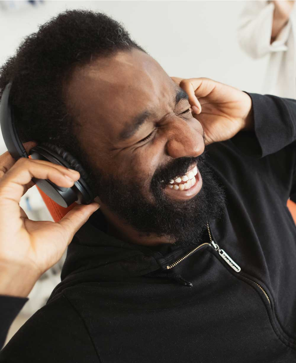 Photo of a man smiling with headphones on