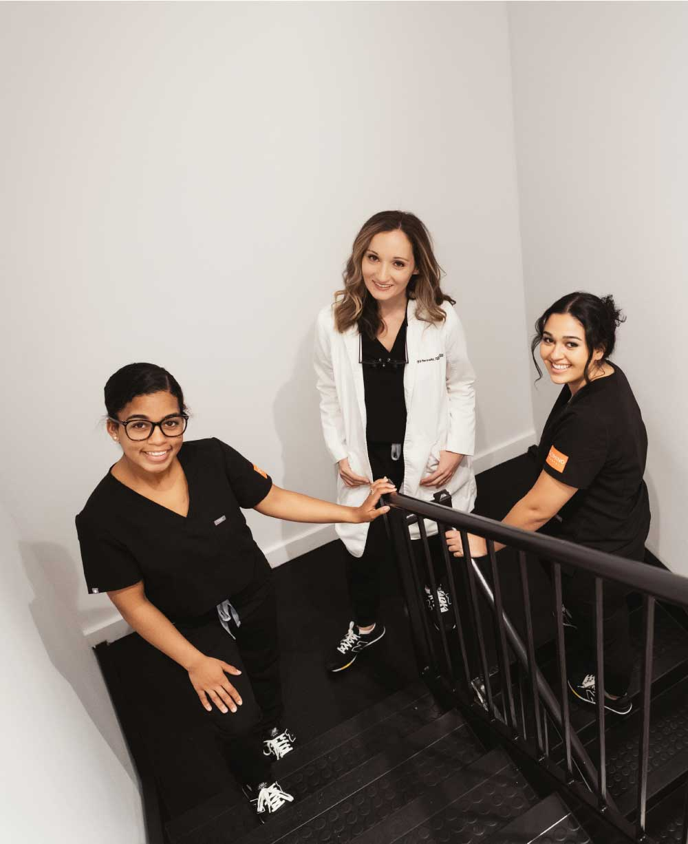 Photo of Dr. Lilya and two team members standing in a stairwell